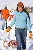 Couple with snowman pulling sled in snowy field