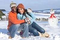 Couple with snowman in snowy field