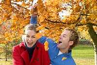 Laughing couple throwing autumn leaves