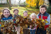 Smiling children holding handfuls of autumn leaves