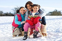Mother and daughters sitting on sled in snowy field
