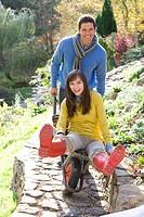 Playful husband pushing wife in wheelbarrow