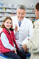 Pharmacist helping girl with asthma inhaler as mother watches