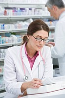 Pharmacist researching medicine in book in pharmacy