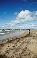 Latvia, Eastern Europe, Baltic States, Western Latvia, Liepaja, Man Walking On Blue Flag Beach