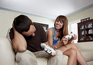 Hispanic husband and wife playing video game