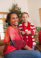 Mixed race mother and daughter sitting by Christmas tree