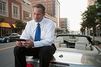 Caucasian businessman sitting on car text messaging on cell phone