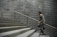 Chinese businessman running up stairs