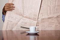 Man checking on his share portfolio in the paper with a coffee in front of him
