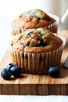 Two blueberry muffins on chopping board