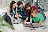 Friends sitting on the floor with notebook and travel brochures