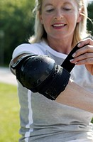 Senior woman tightening elbow pad, front view, close_up