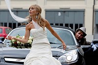 Bride in front of a car, bridegroom in the background