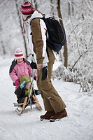 woman pulling children with sled