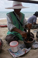 Thai woman preparing a Thai style salad at the Beach