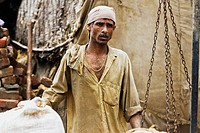 Man holding straw sacks for weighing in a straw store, Delhi, India