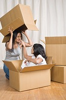 Woman and her daughter playing with cardboard boxes