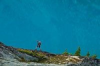 A young woman hikes in front of a blue lake in the Niut Range, British Columbia, Canada