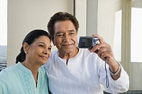 Couple taking a picture of themselves with a digital camera