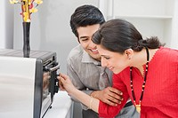 Couple adjusting control of microwave oven in the kitchen