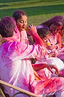 Family celebrating Holi with traditional Indian cuisines