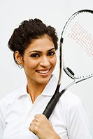 Portrait of a young woman holding a tennis racket and smiling