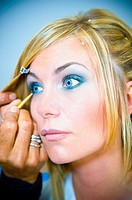 Make-up artist applying blue eye liner on a woman