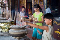 Children burning incense in The Cheng Hoon Teng Temple on Jalan Tokong Chinatown Malacca