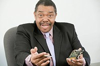 Portrait of a businessman holding a computer chip and a pen