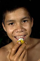 Portrait of a boy eating Charichuela fruit, Rio Pucate, Loreto Region, Peru