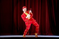 clown performing on stage playing guitar