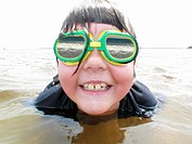 a child swimmer with reflections in her goggles