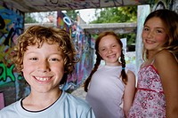 portrait of three young children at playground