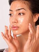 Woman applying liquid on her face