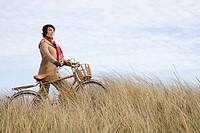 Woman in field with bicycle