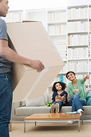 Man unpacking whilst woman and girl sit on sofa (thumbnail)