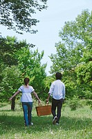 Couple Walking in Park Holding Basket