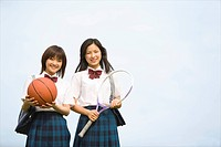 High school girls holding tennis racket and basketball
