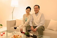 Couple sitting on a sofa with wine and appetizers