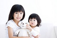 Girl holding her baby sister and a teddy bear
