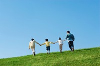 Rear view of family of four walking and holding hands at the park against a blue sky