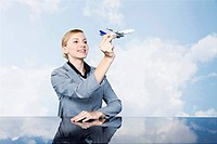 Businesswoman holding toy plane