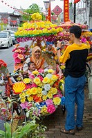 A Malaysian tourist photographs his wife and child amongst the colourful decorations of a trishaw in Malacca