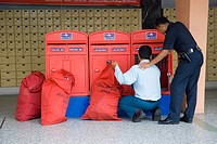 Postman emptying letter boxes at the central Post Office in Johor Baru Malaysia