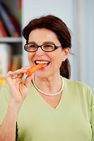 Elderly woman eating a carrot