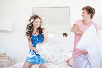 Couple pillow fighting in bedroom