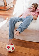 Man laying on sofa with foot on soccer ball (thumbnail)