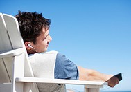 Man sitting in deck chair listening to headphones with eyes closed