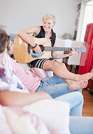 Woman with bare feet playing guitar for men on sofa